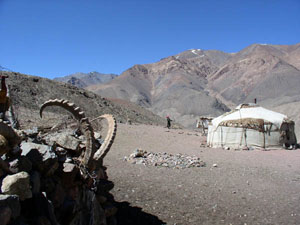 a herder's yurt with an Ibex horn hanging on a nearby rock wall