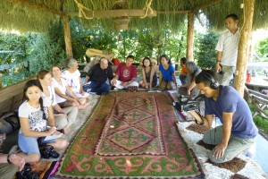 Workshop members gathered around a Kyryz rug