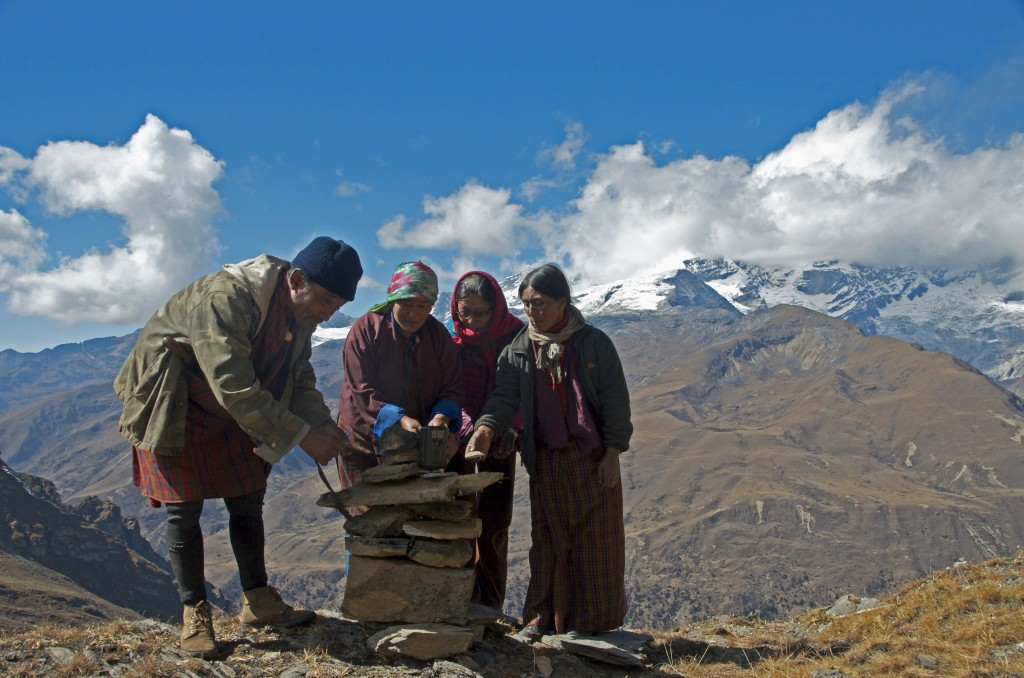 three women and one man setting a camera trap on a ridge