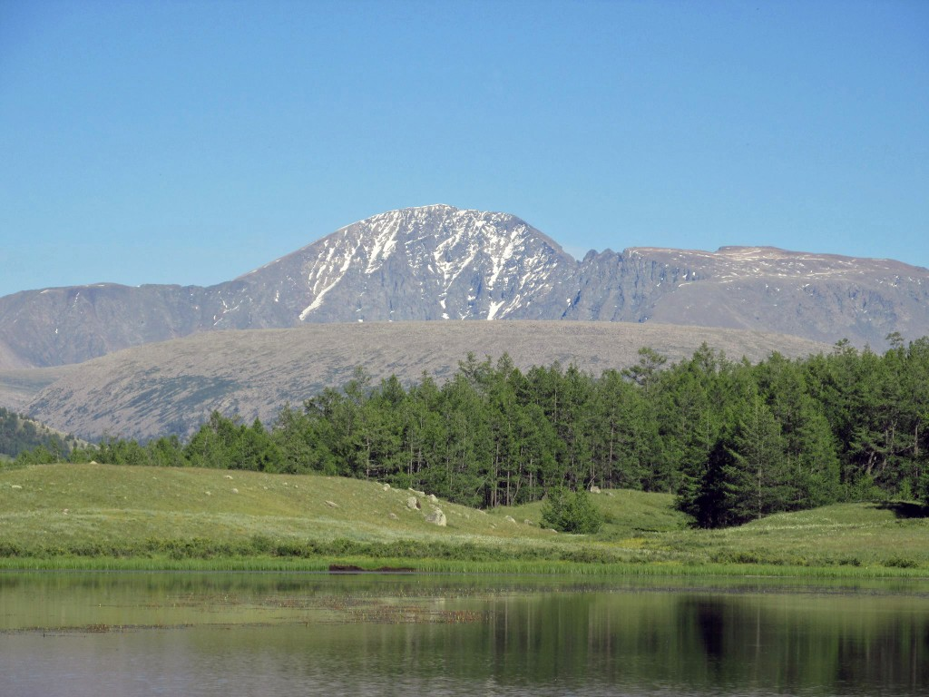 Mountain with green hills, trees and lake in foreground