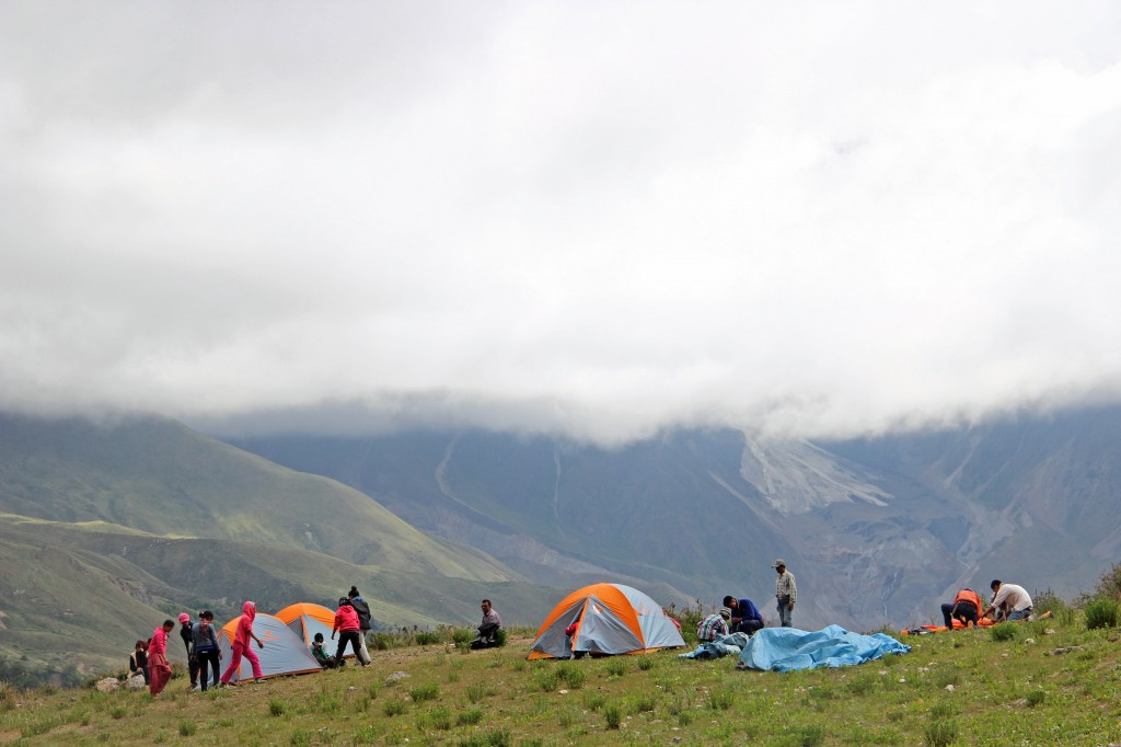 tents being set up with mountains in the background