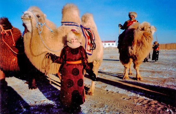 Janet in Mongolian dress next to a camel