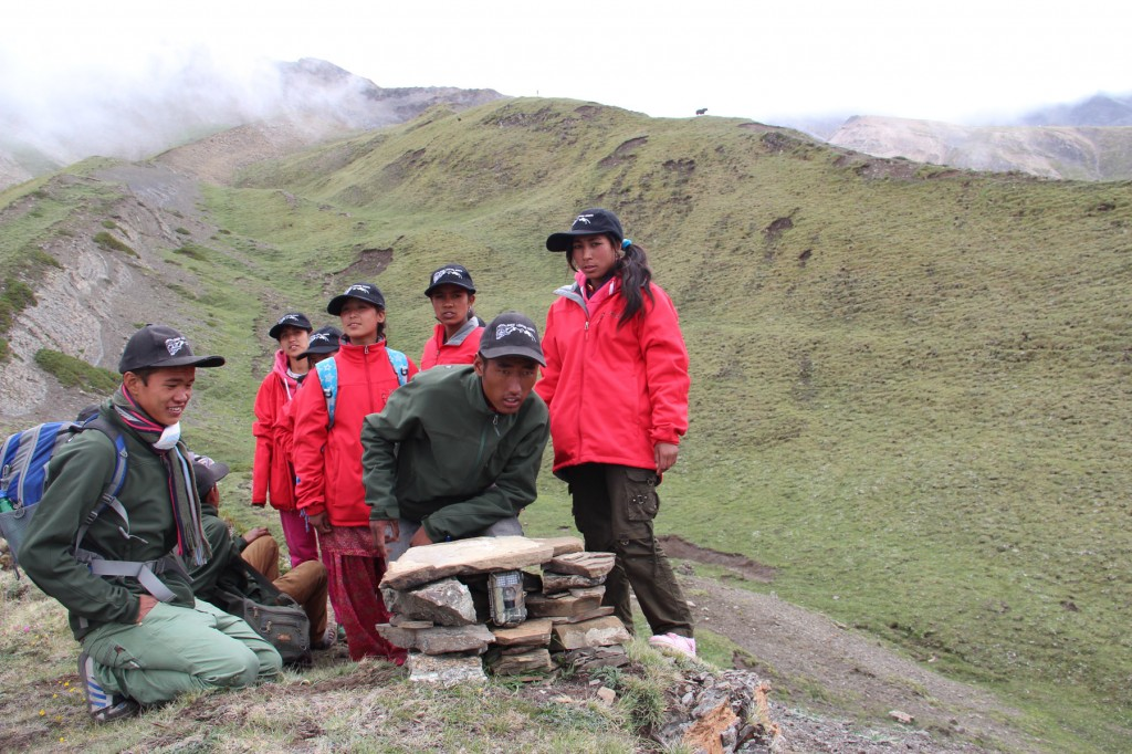 Group of 8 snow leopard scouts setting up a trail camera