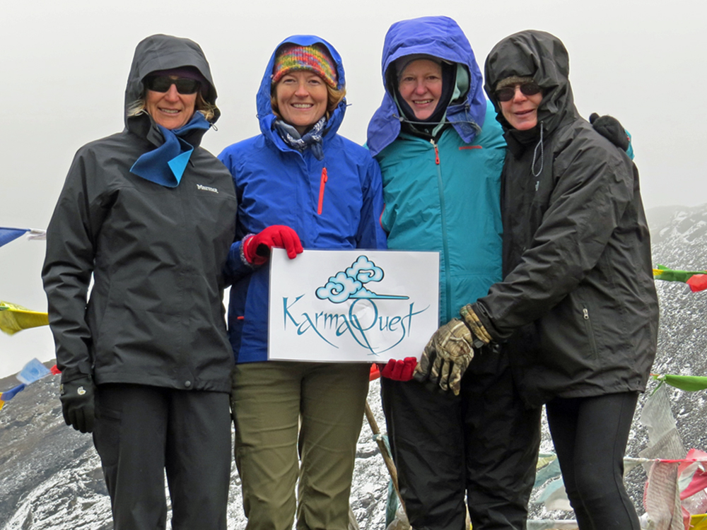 Four women standing together holding a sign reading KarmaQuest. Snow and prayer flags in background
