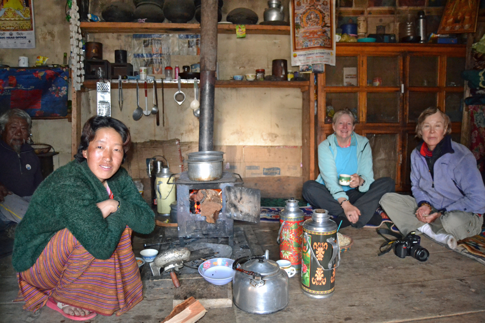 Nancy, Caroline, and Bhutanese woman sitting near woodburning stove