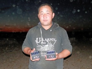 Mongolian man holding  two predator guards and posing for camera