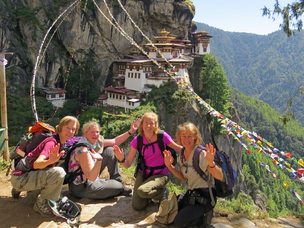 Four women posing with Taktshang Monastery on the cliff behind them