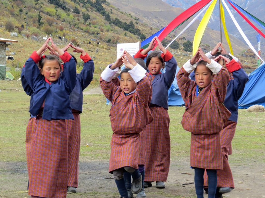 Several Bhutanese children in traditional dress performing a dance