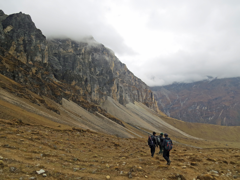 Three people hiking amidst sheer cliffs and grassy plain