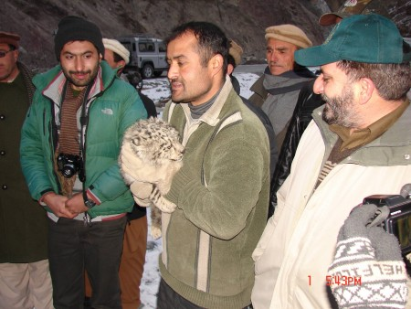 Man holding snow leopard cub with other men around him