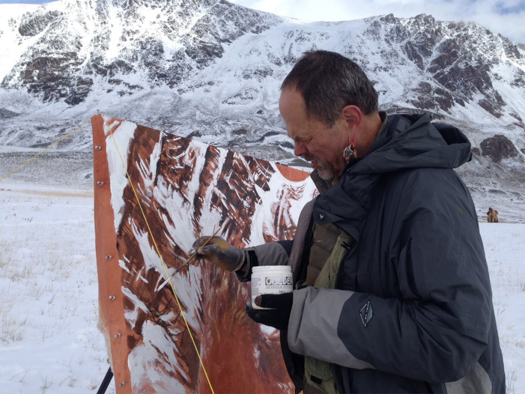 Joe painting on a canvas with snow covered mountains and ground surrounding him