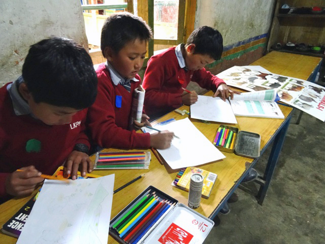 Three young boys sitting a table and drawing pictures