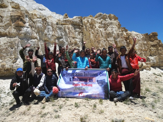 Large group of people holding a sign saying snow leopard environmental camp with rocky cliffs in background