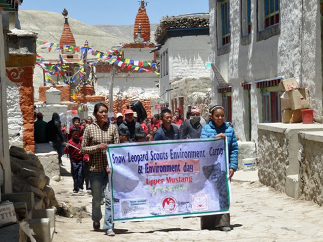 group of people carrying a banner saying snow leoaprd scouts environment camp on a cobblestone street between buildings