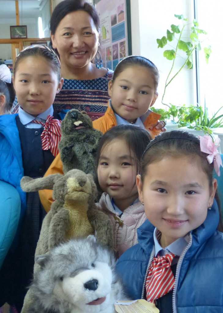 Tunga with 4 young students standing in front of her holding puppets